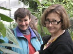 Sue von Salis and Kathy Durning in the greenhouse, with Gately in the background.